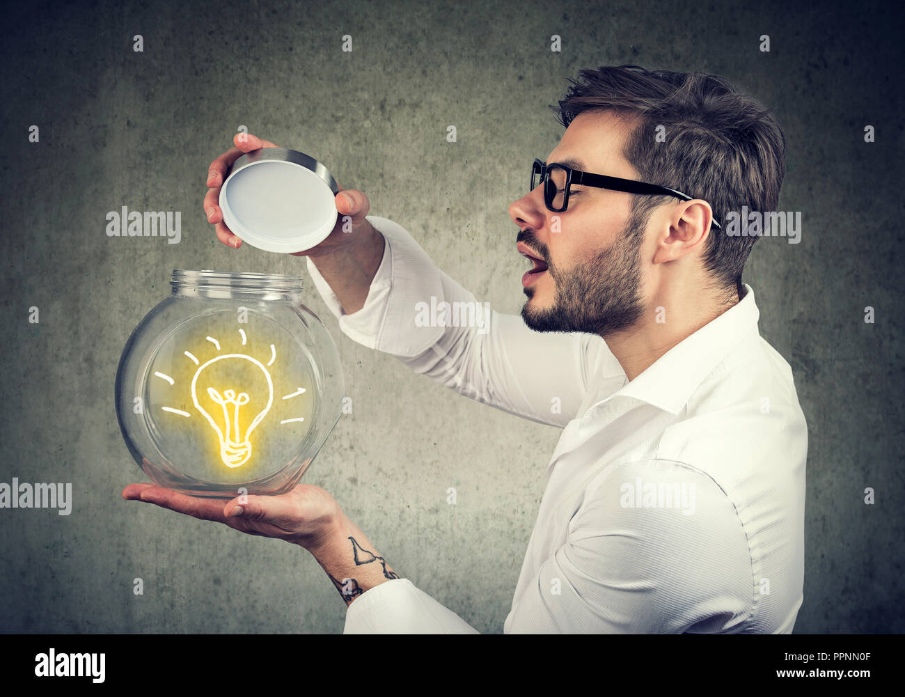 Excited man holding opening a glass jar with bright idea lighbulb inside being creative - Stock Image