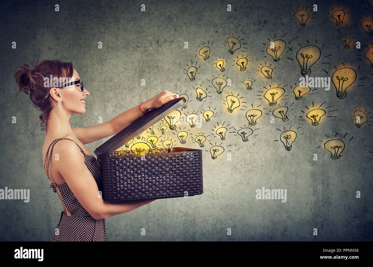 Side view of young happy woman holding a box with brilliant ideas spreading knowledge - Stock Image