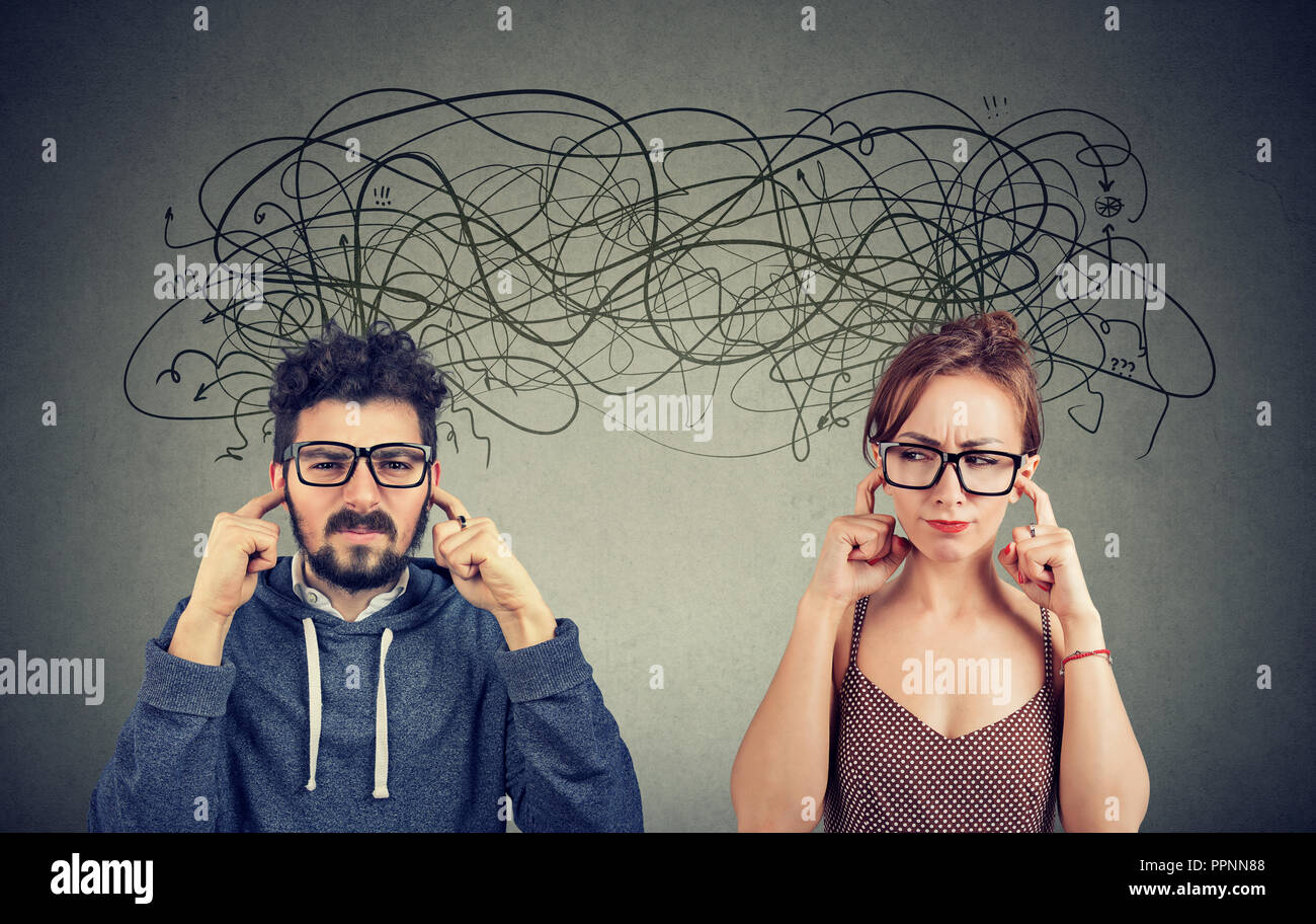 Angry displeased couple woman and man ignoring not listening each other exchanging with many negative thoughts - Stock Image