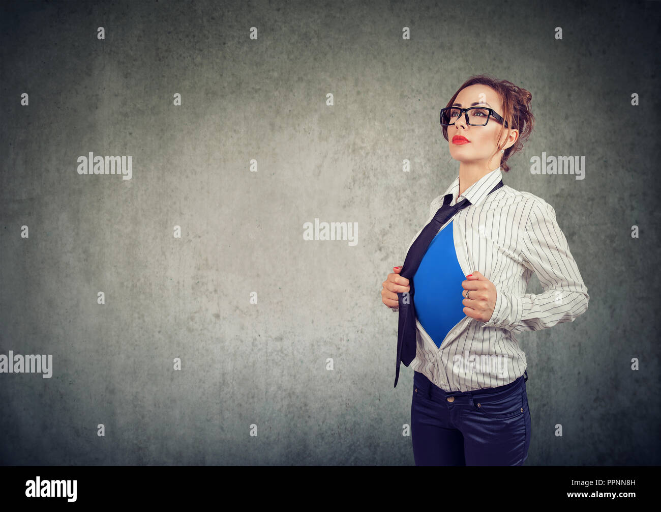 Businesswoman showing a super hero suit underneath her shirt - Stock Image