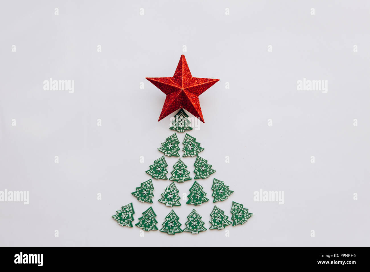 creative idea in minimalistic style for christmas or new year themes christmas tree from other small wooden christmas trees and a star on top