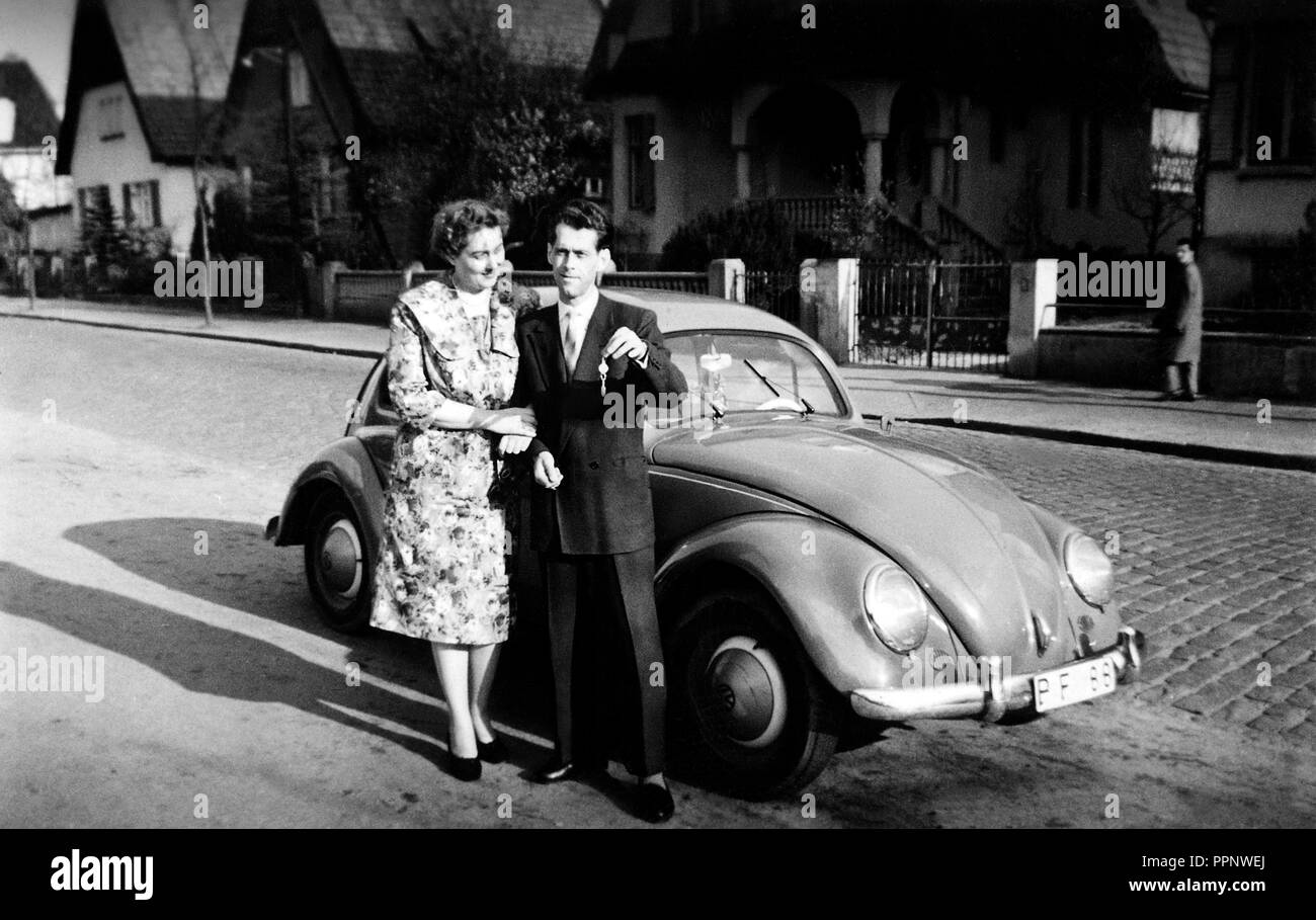 Couples, man and woman stand proudly in front of their first car, a VW Beetle, 1950s, Germany - Stock Image