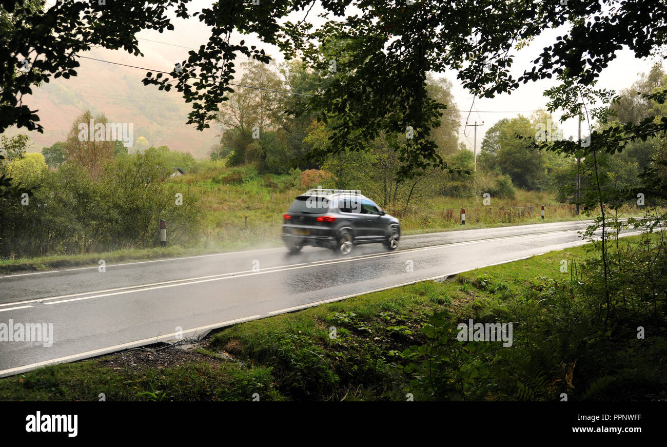 CAR TRAVELLING NEAR GLENCOE SCOTLAND RE BENDS IN ROAD THE HIGHLANDS DRIVING REMOTE LOCATIONS WET ROADS SCOTTISH UK - Stock Image