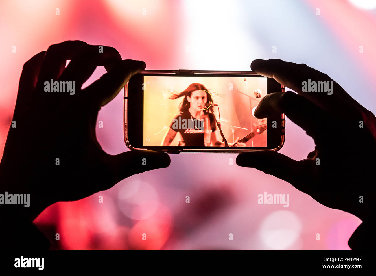 Fan taking photo with cellphone of musician, Brazilian band thrash metal band Nervosa, Lucerne, Switzerland - Stock Image