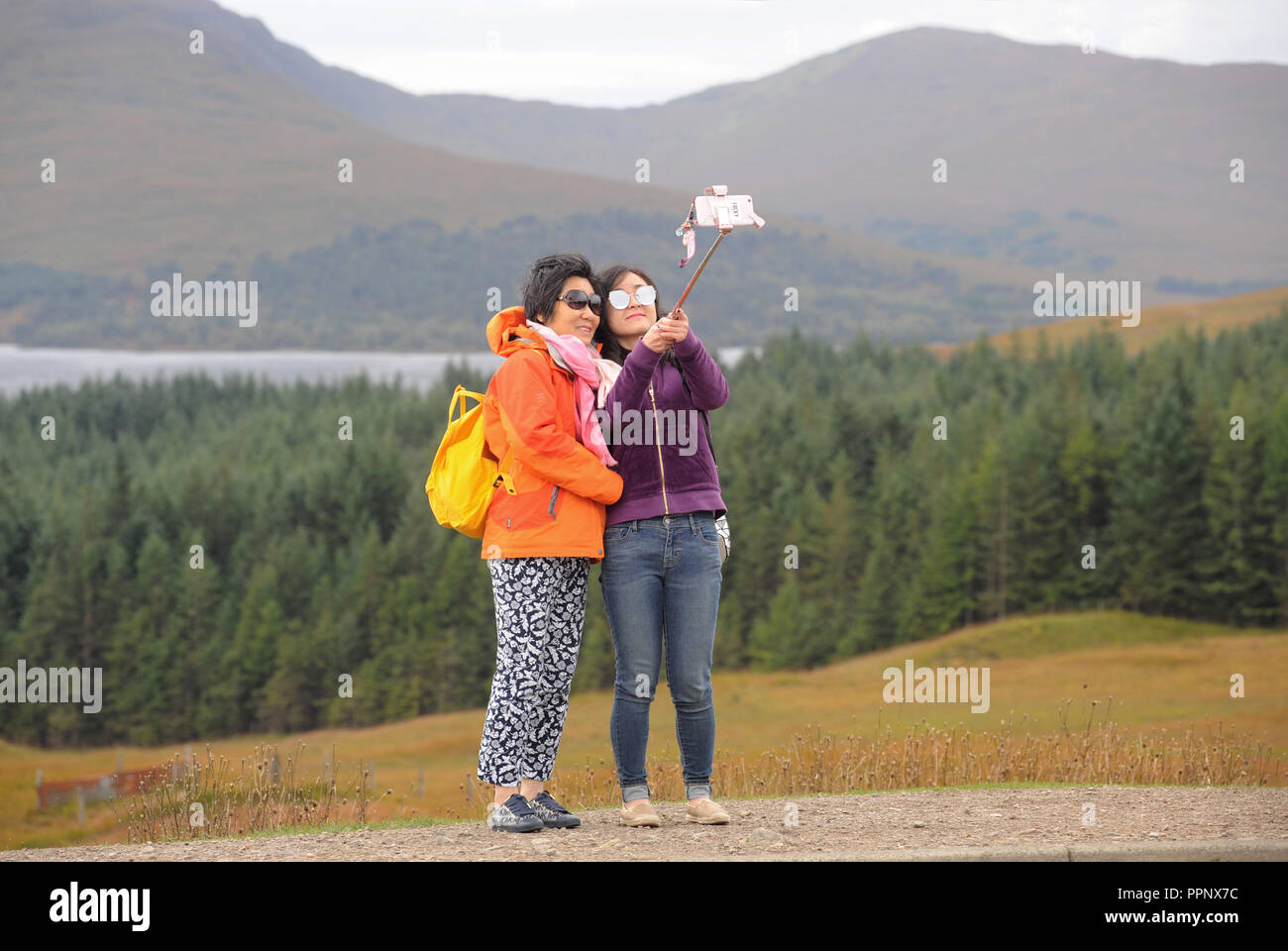 JAPANESE TOURISTS TAKING SELFIE PHOTOGRAPHS IN THE SCOTTISH HIGHLANDS RE TOURISM TOURING COACH TOURS HOLIDAYS VIEWPOINT SCENIC VIEWS UK - Stock Image