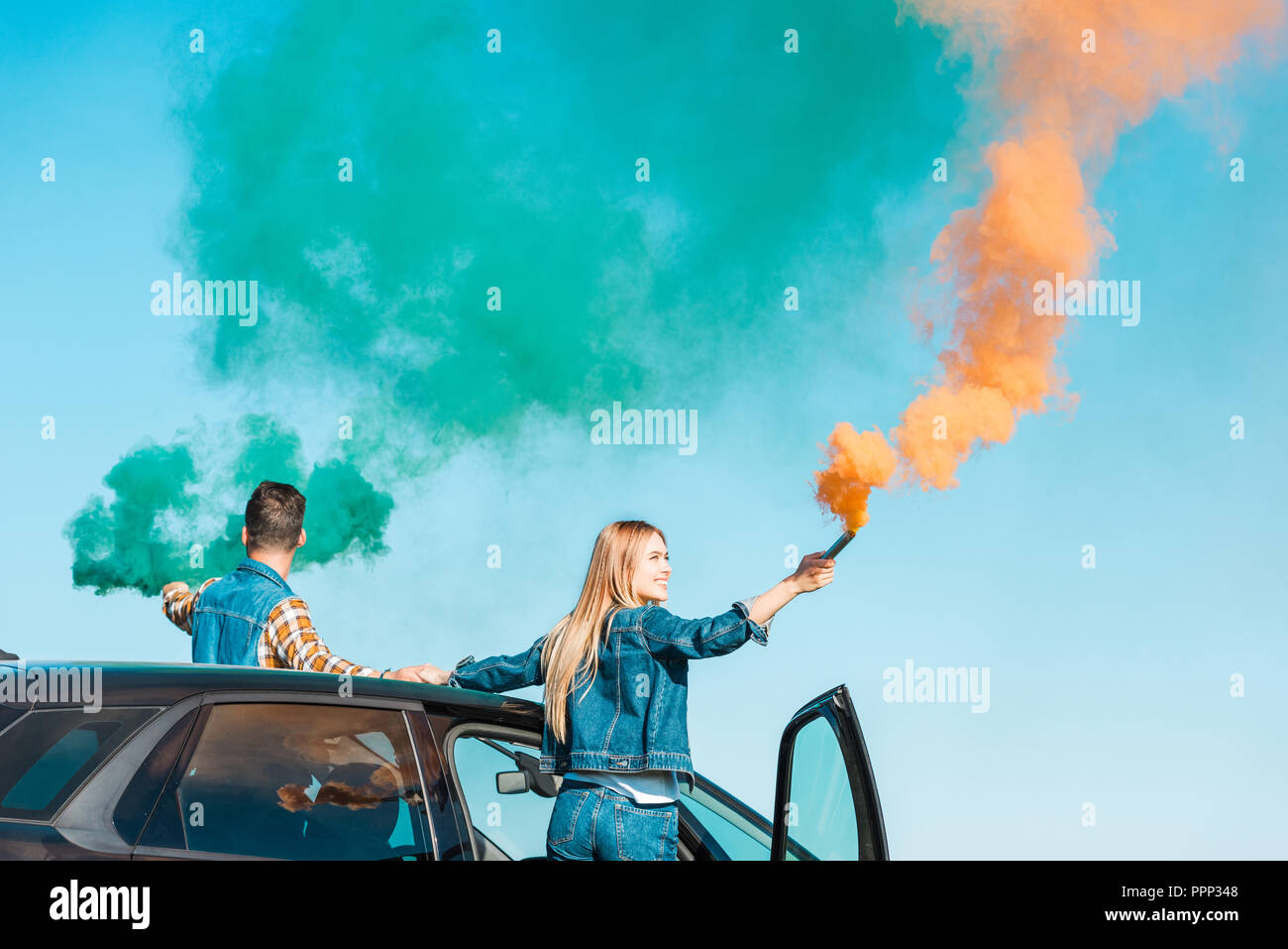 young couple standing on car and holding green and orange smoke bombs - Stock Image