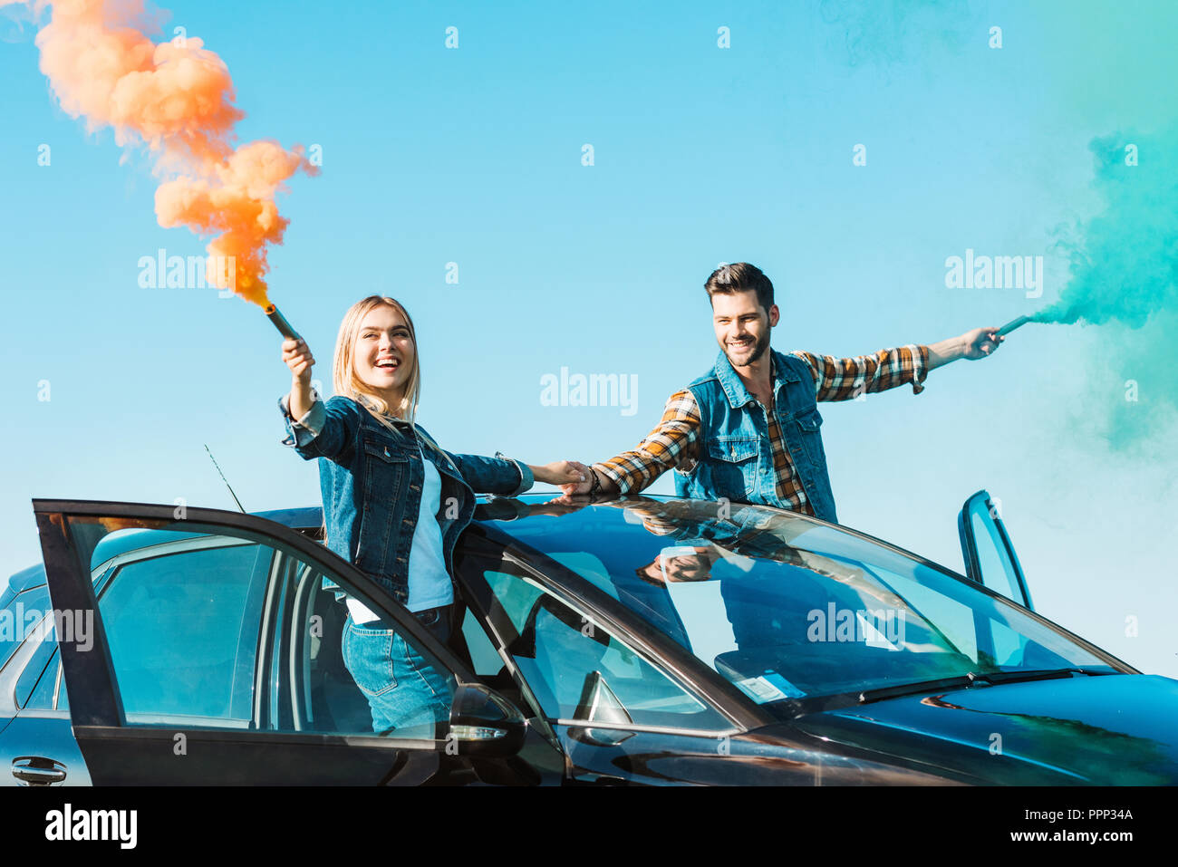 smiling couple standing on car and holding green and orange smoke bombs - Stock Image