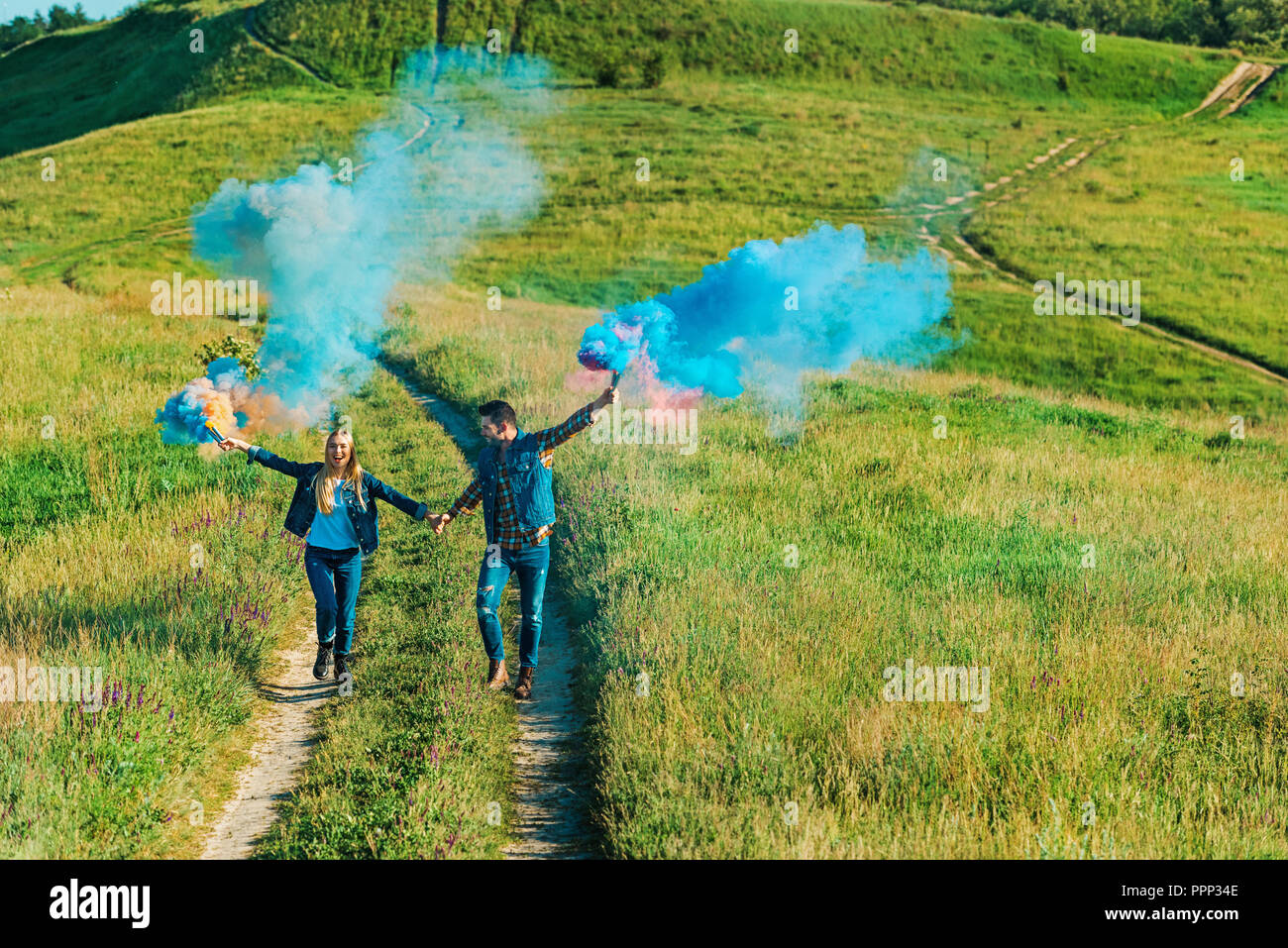 elevated view of couple holding colorful smoke bombs on rural meadow - Stock Image