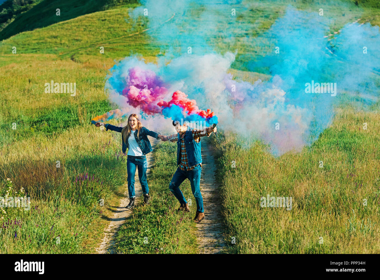 high angle view of couple holding colorful smoke bombs on rural meadow - Stock Image