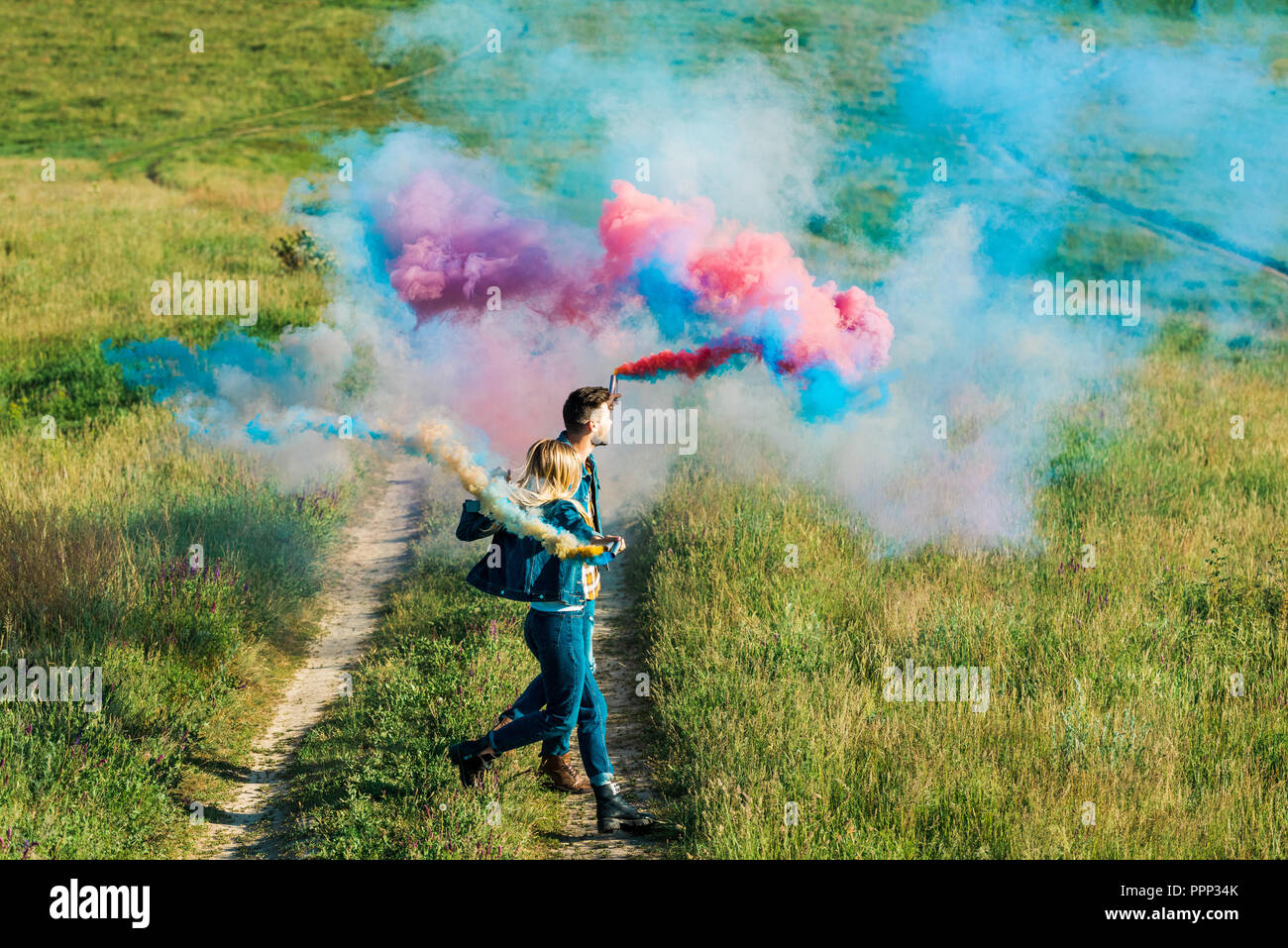 side view of couple holding colorful smoke bombs in field - Stock Image