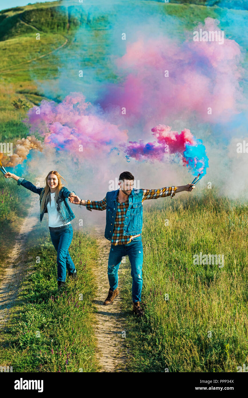 elevated view of smiling couple holding colorful smoke bombs on rural meadow - Stock Image