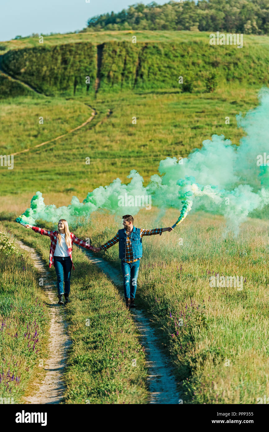 elevated view of young couple holding green smoke bombs on rural meadow - Stock Image