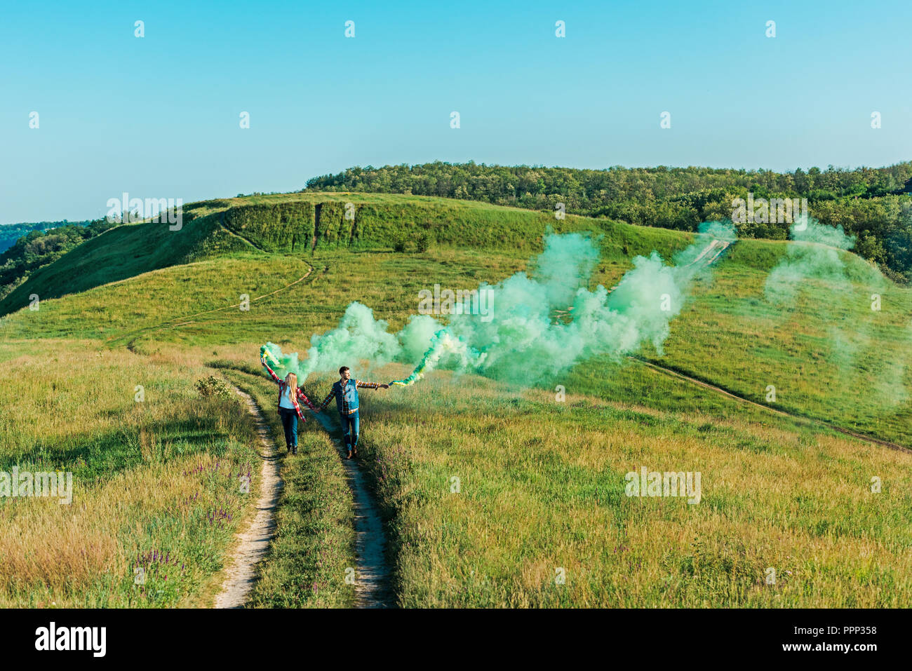 distant view of young couple holding green smoke bombs on rural meadow - Stock Image