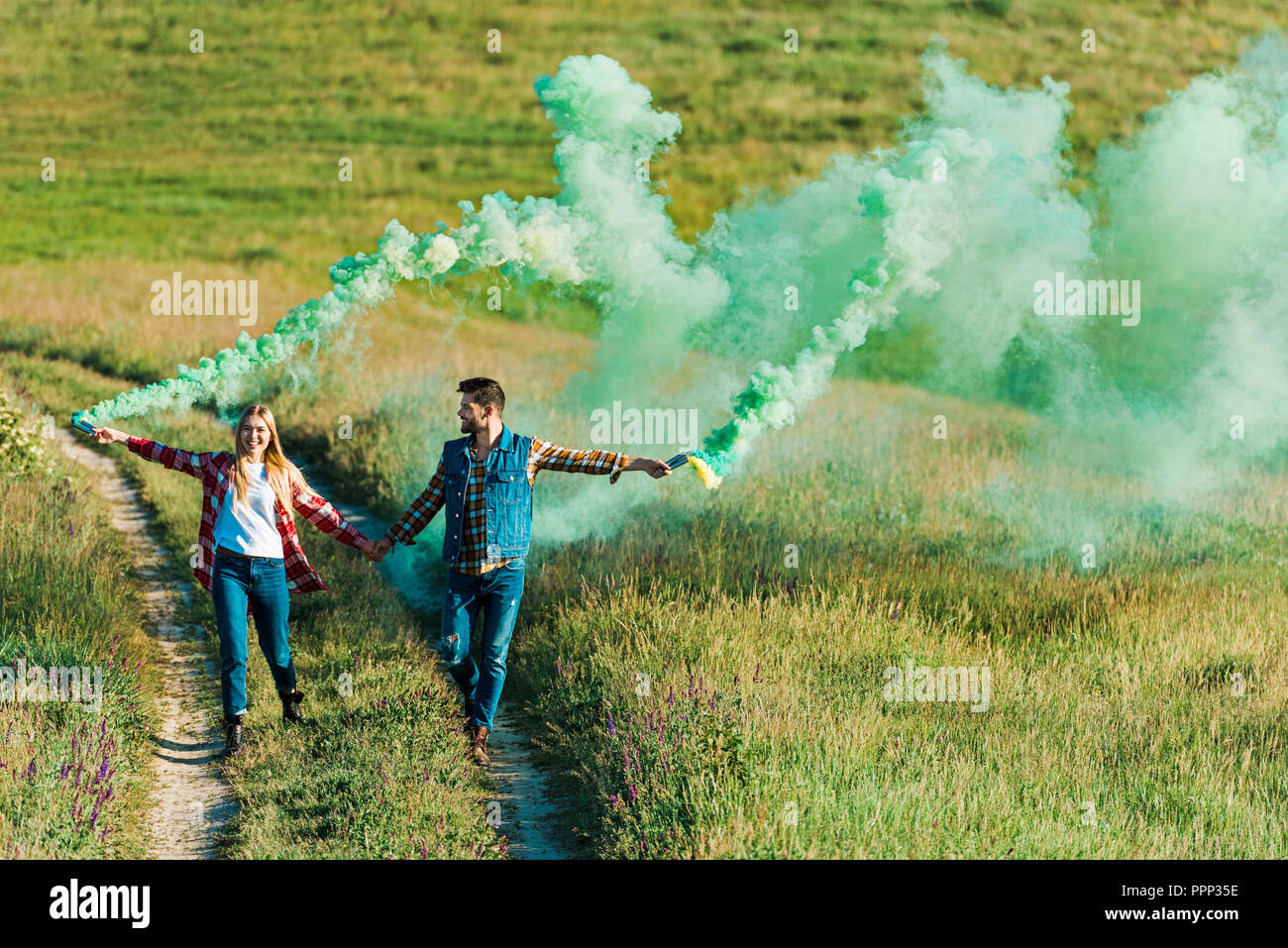 front view of young couple holding green smoke bombs on rural meadow - Stock Image
