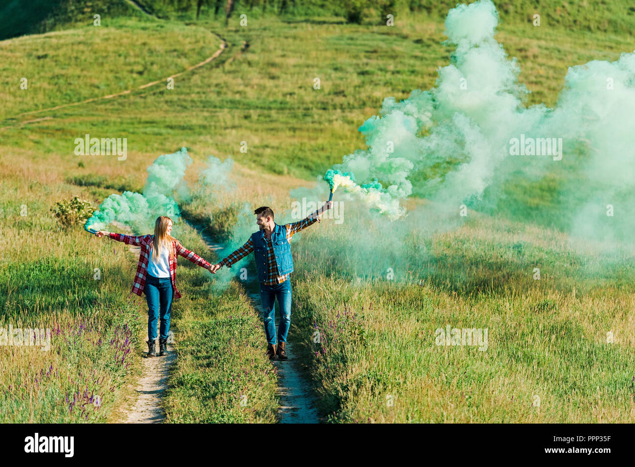 young couple holding green smoke bombs on rural meadow - Stock Image