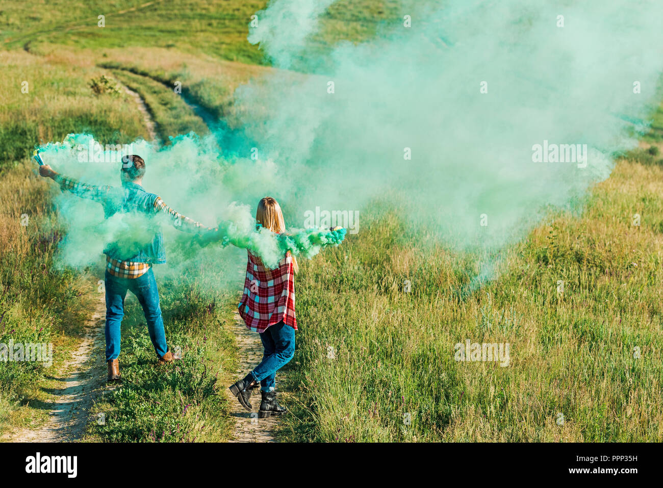 back view of young couple holding green smoke bombs on rural meadow - Stock Image