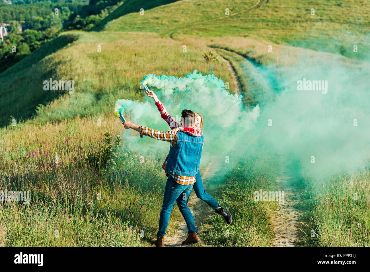 back view of man holding girlfriend and green smoke bombs on rural meadow - Stock Image