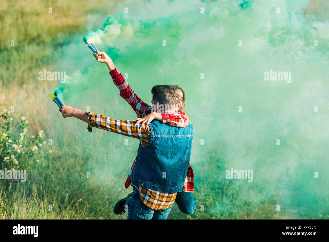 rear view of man holding girlfriend and green smoke bombs in field - Stock Image