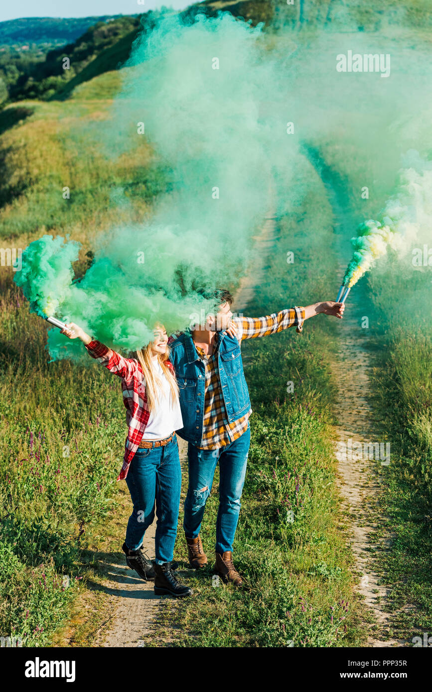 elevated view of young couple holding green smoke bombs in field - Stock Image
