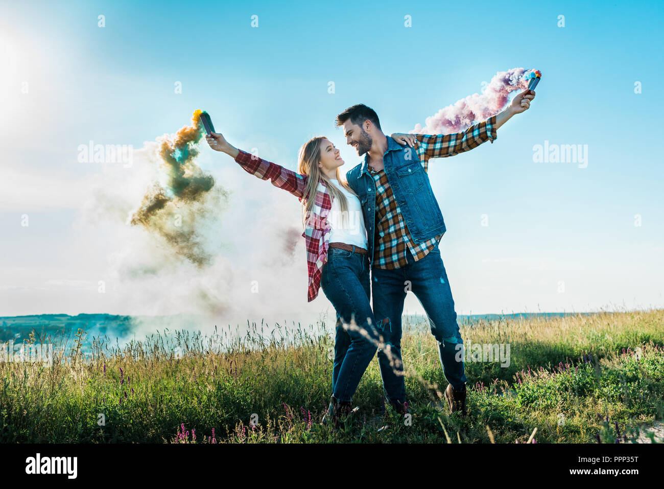 young couple looking at each other and holding colorful smoke bombs on rural meadow - Stock Image