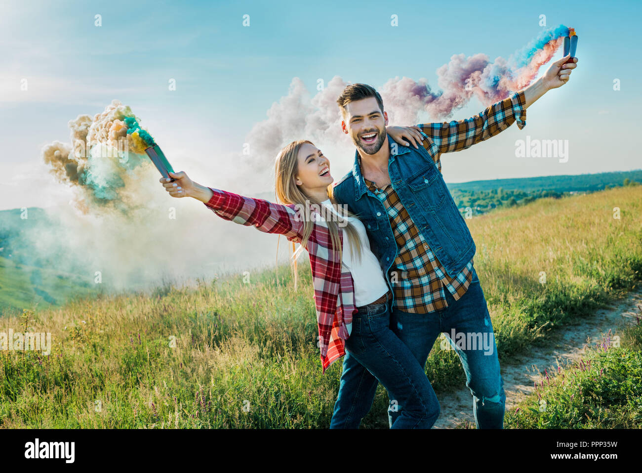 young couple holding colorful smoke bombs on rural meadow - Stock Image
