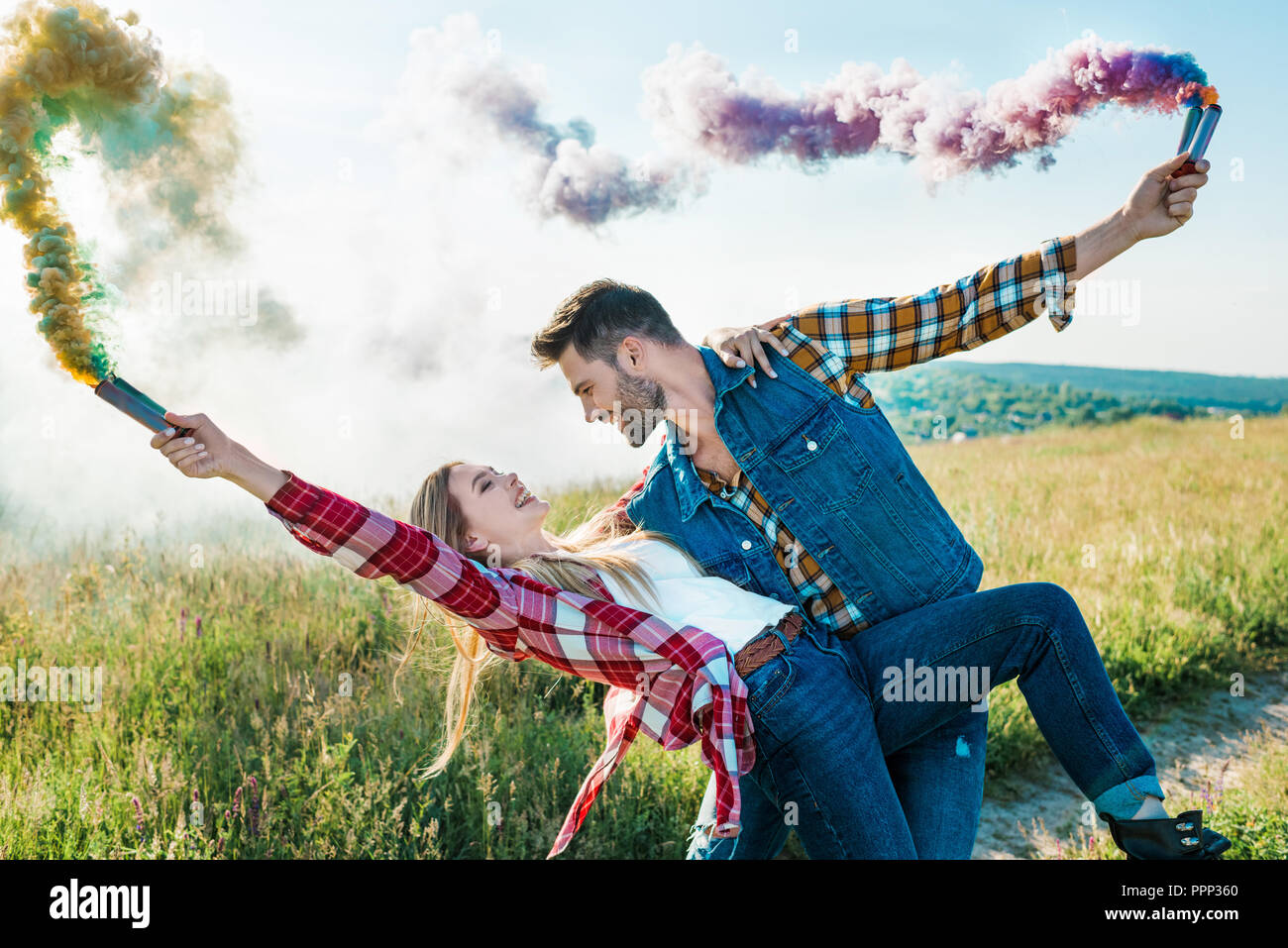 side view of man with colorful smoke bombs holding girlfriend back in rural field - Stock Image