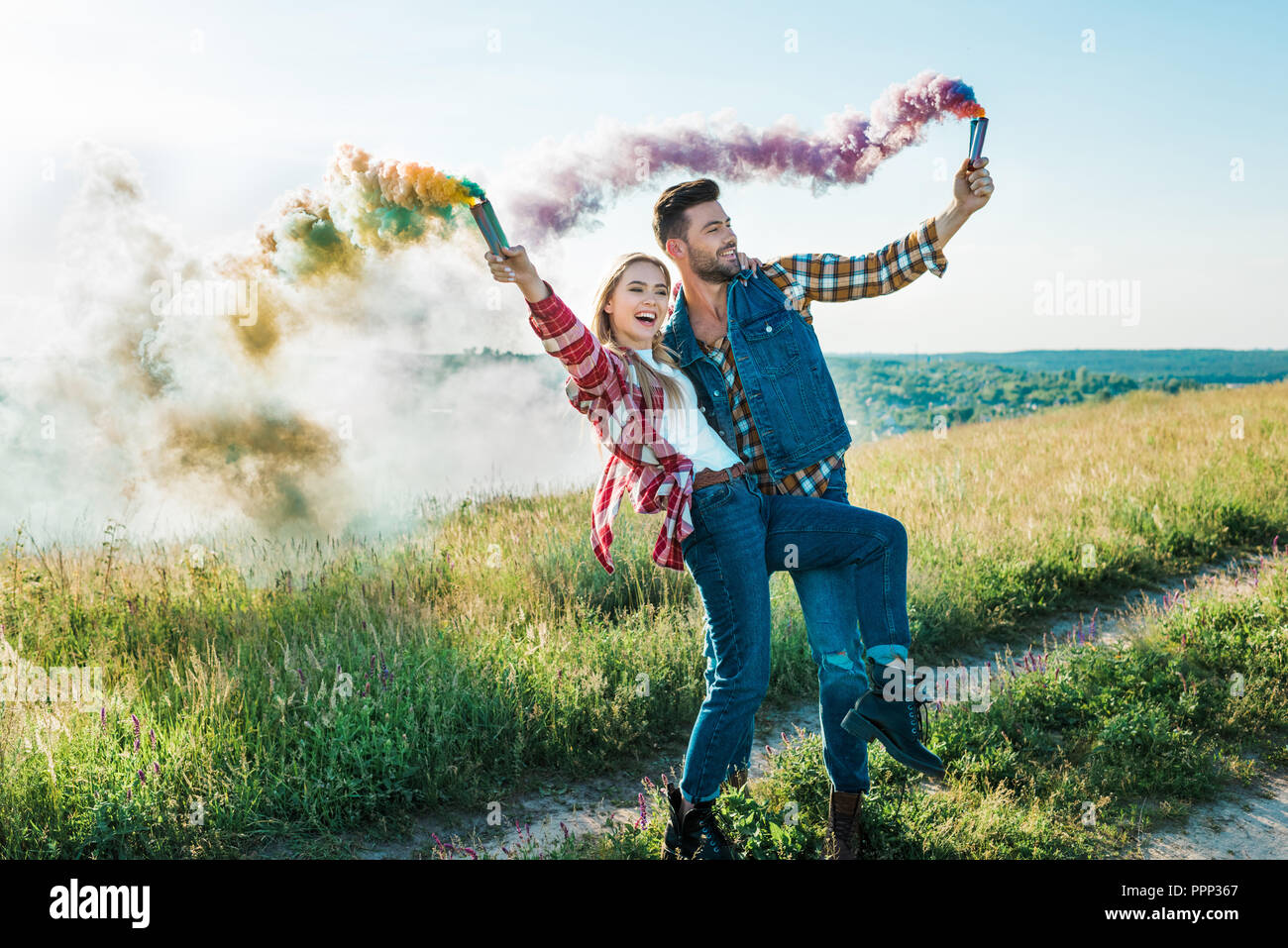 happy young couple holding colorful smoke bombs on rural meadow - Stock Image