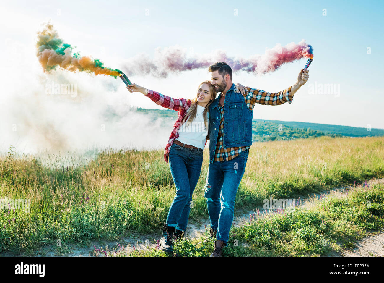 young couple holding colorful smoke bombs in field - Stock Image