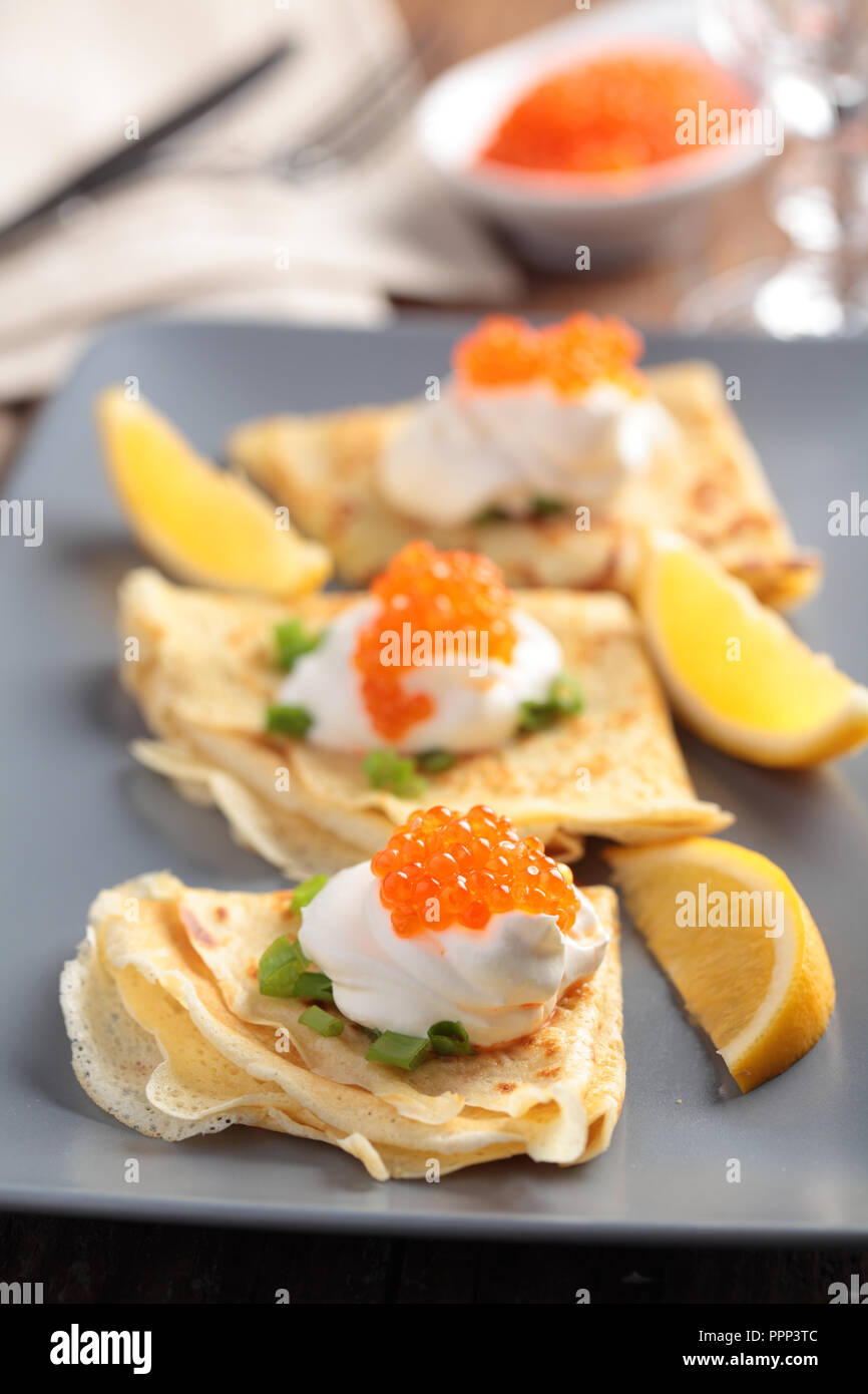 Crepes with red caviar on a plate - Stock Image