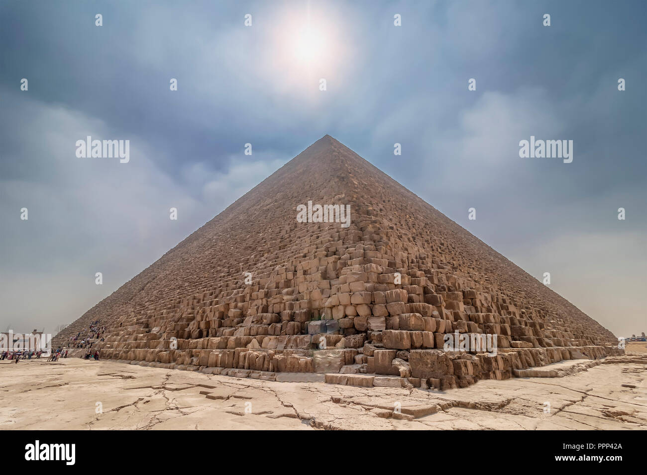 The Pyramid of Cheops illuminated by the sun in backlight, with people entering inside to visit it. The area with the great pyramids of Giza, Egypt - Stock Image