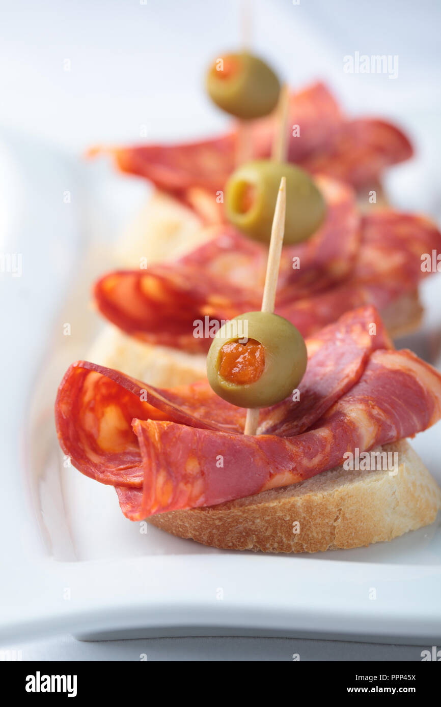 Canapes with chorizo and green olives stuffed with paprika - Stock Image