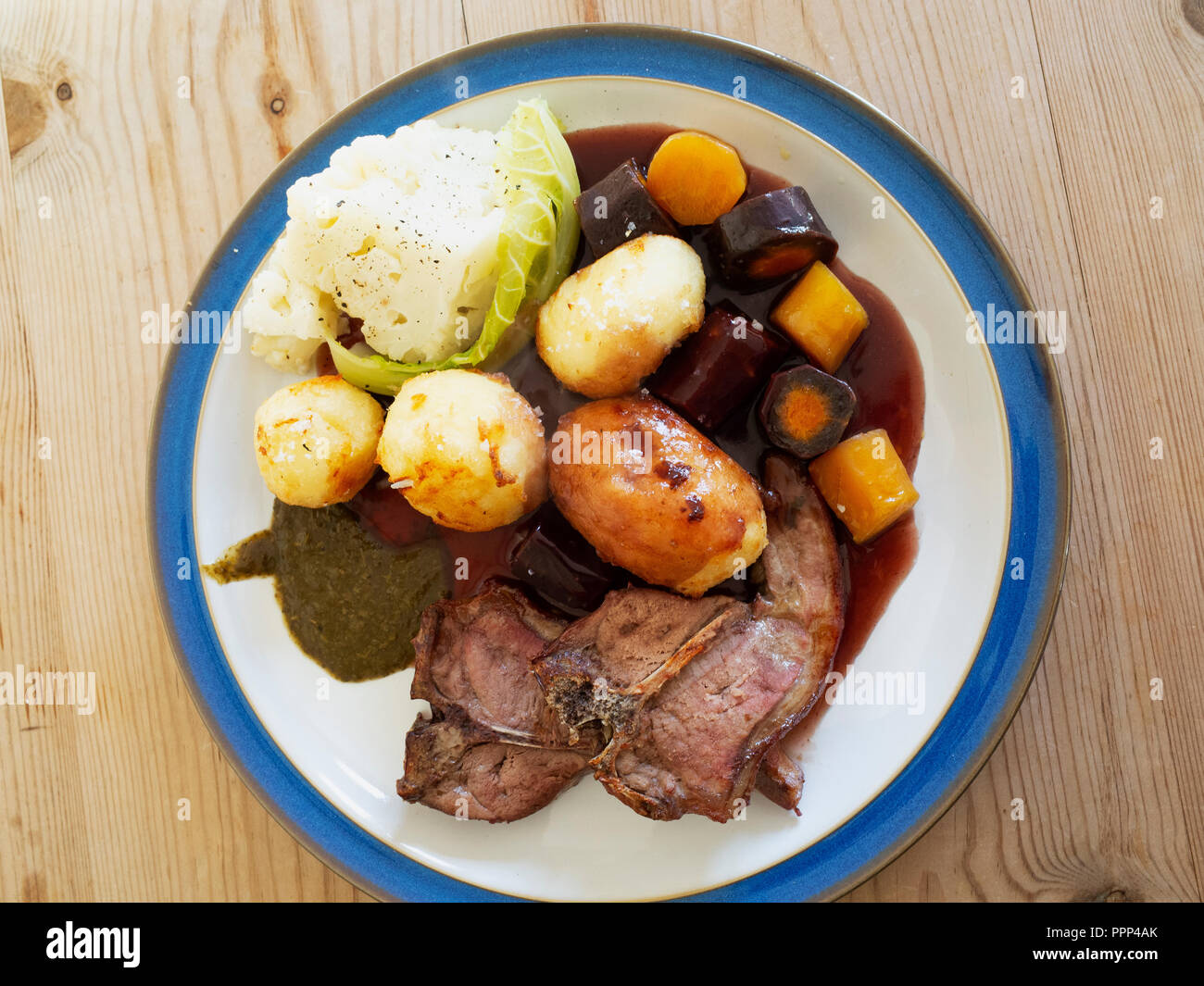 English lunch  dinner meal lamb chops roast potatoes cauliflower roasted carrots red wine gravy and mint sauce blue edge white plate on a wooden table Stock Photo