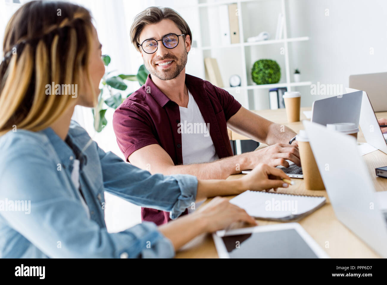 smiling colleagues working on startup project in office and looking at each other Stock Photo