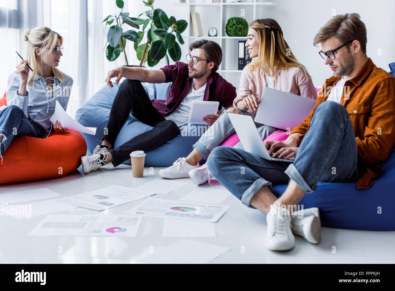 young multicultural colleagues discussing startup project in office - Stock Image