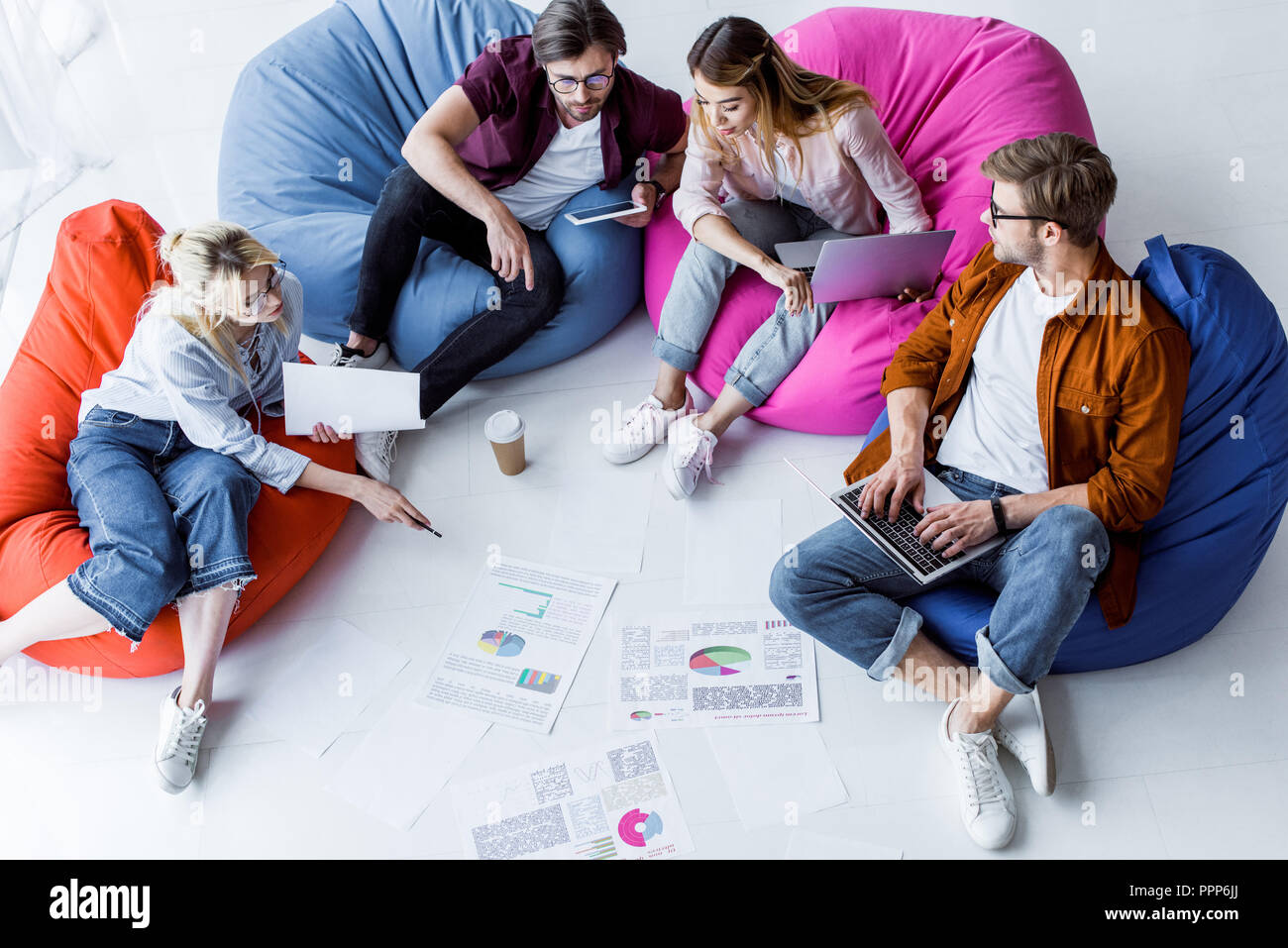 high angle view of multicultural colleagues discussing startup project in office - Stock Image
