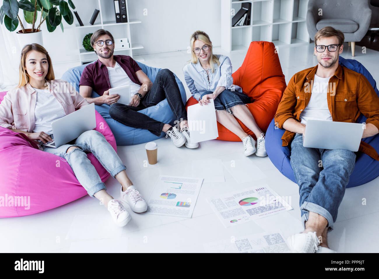 multicultural colleagues working on startup project in office and sitting on bean bag chairs with gadgets - Stock Image