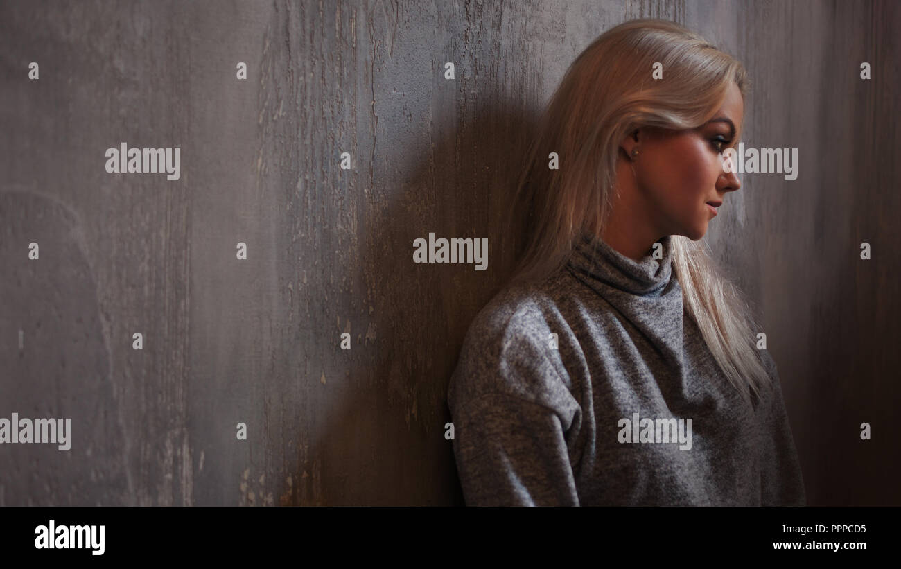 Depressed woman. blonde girl sitting on the floor, sadness and depression, concept of psychological problem - Stock Image