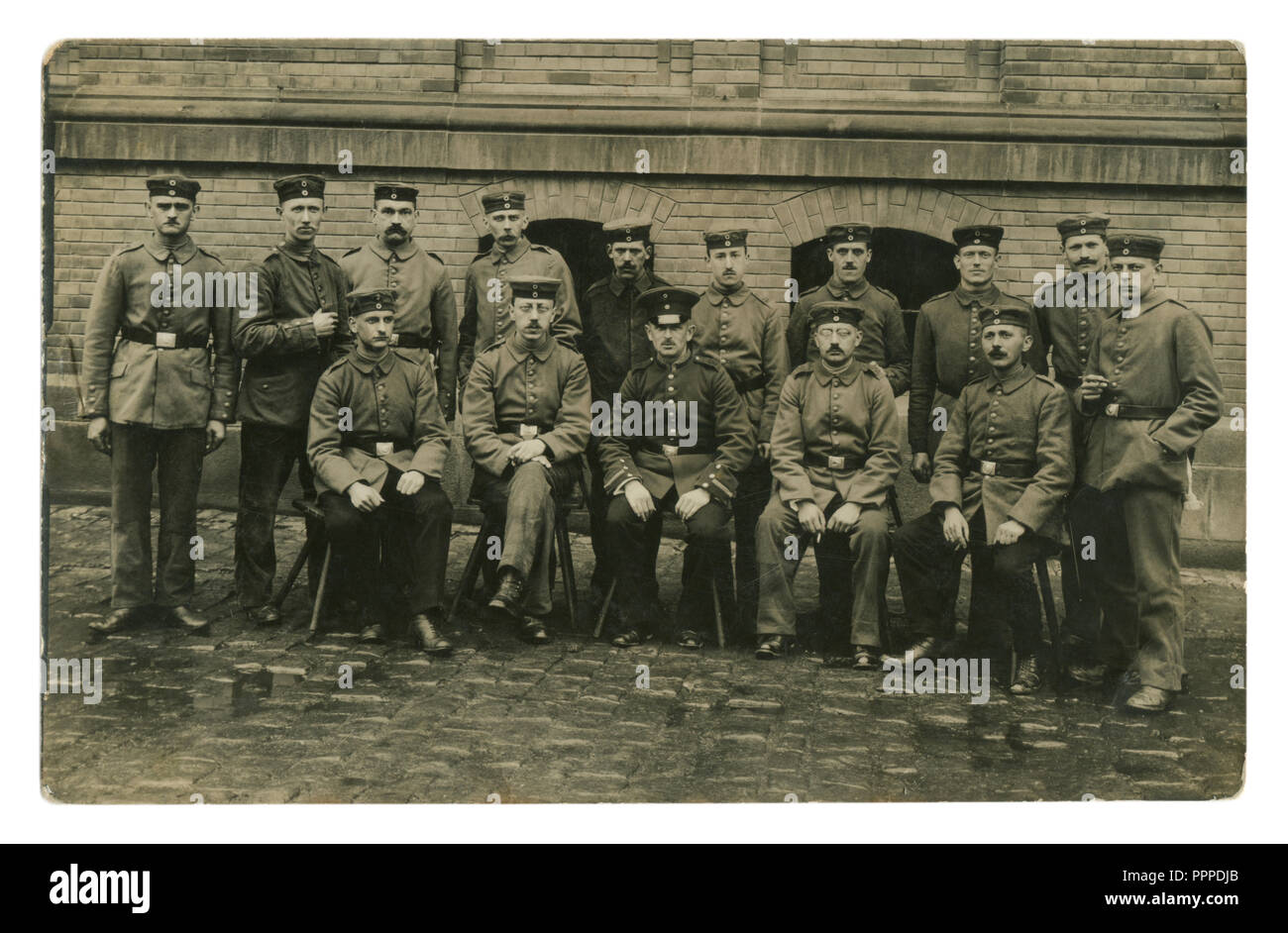 German historical photo: group portrait of a military unit, the soldiers and the officer smoke cigarettes, against a brick wall. world war one 1914-18 - Stock Image