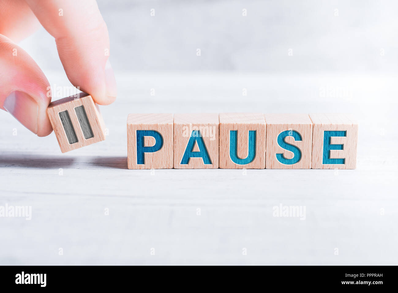 The Word Pause Formed By Wooden Blocks And Arranged By Male Fingers On A White Table - Stock Image