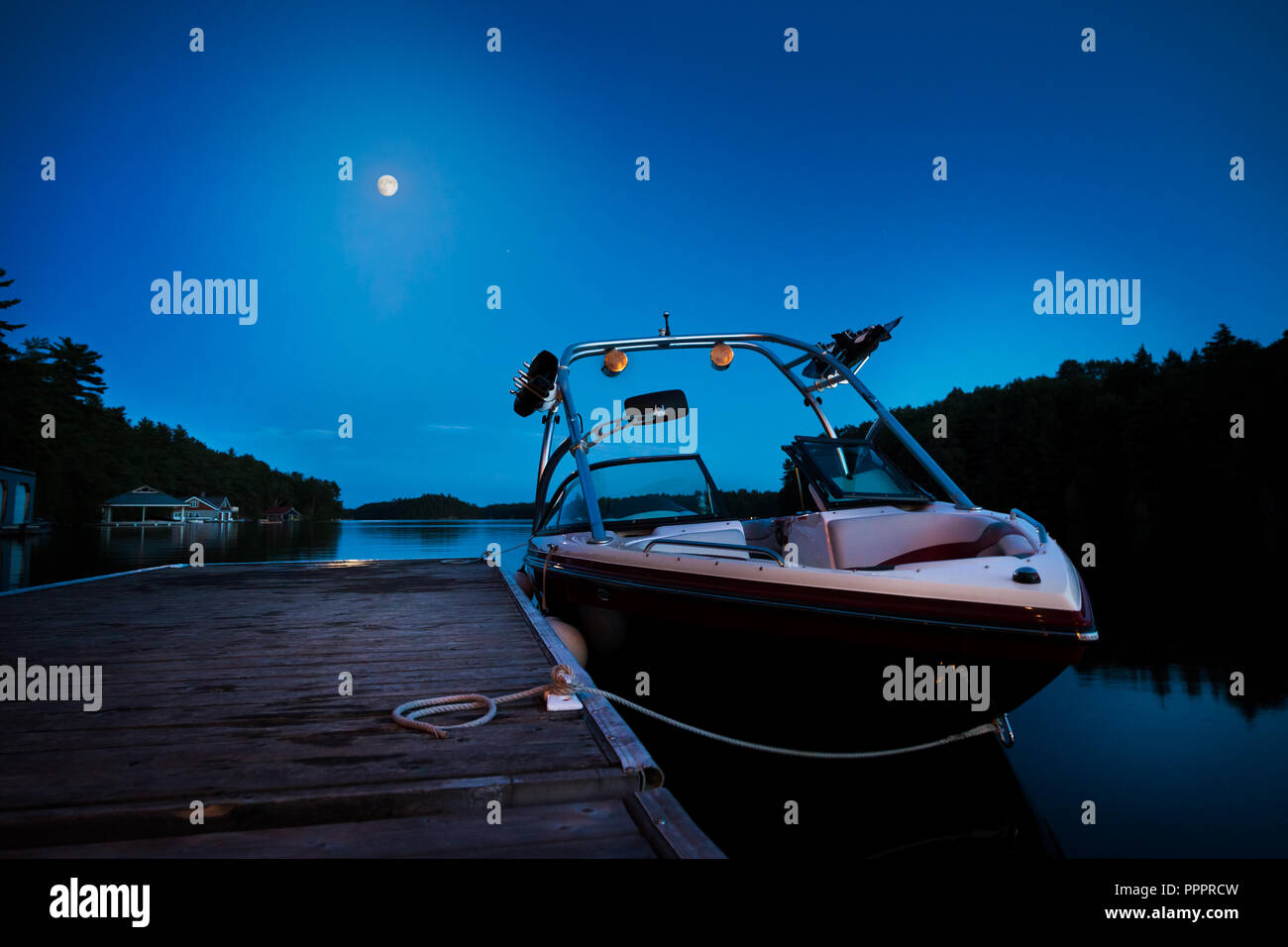 A wakeboard boat docked on Lake Joseph in the evening with the moon in the background. - Stock Image