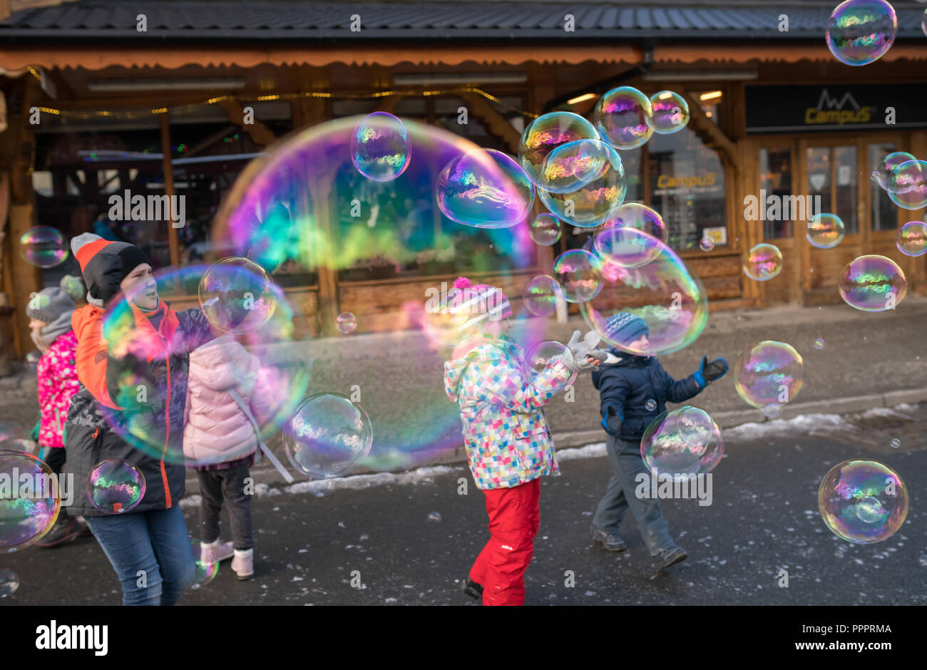 Karpacz, Poland - February 2018 : Children trying to catch giant soap bubbles on the main high street in Karpacz town, polish winter ski resort Stock Photo