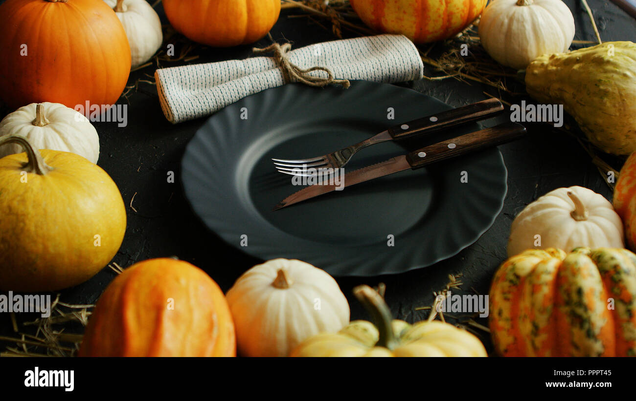 Black plate and cutlery surrounded by pumpkins - Stock Image
