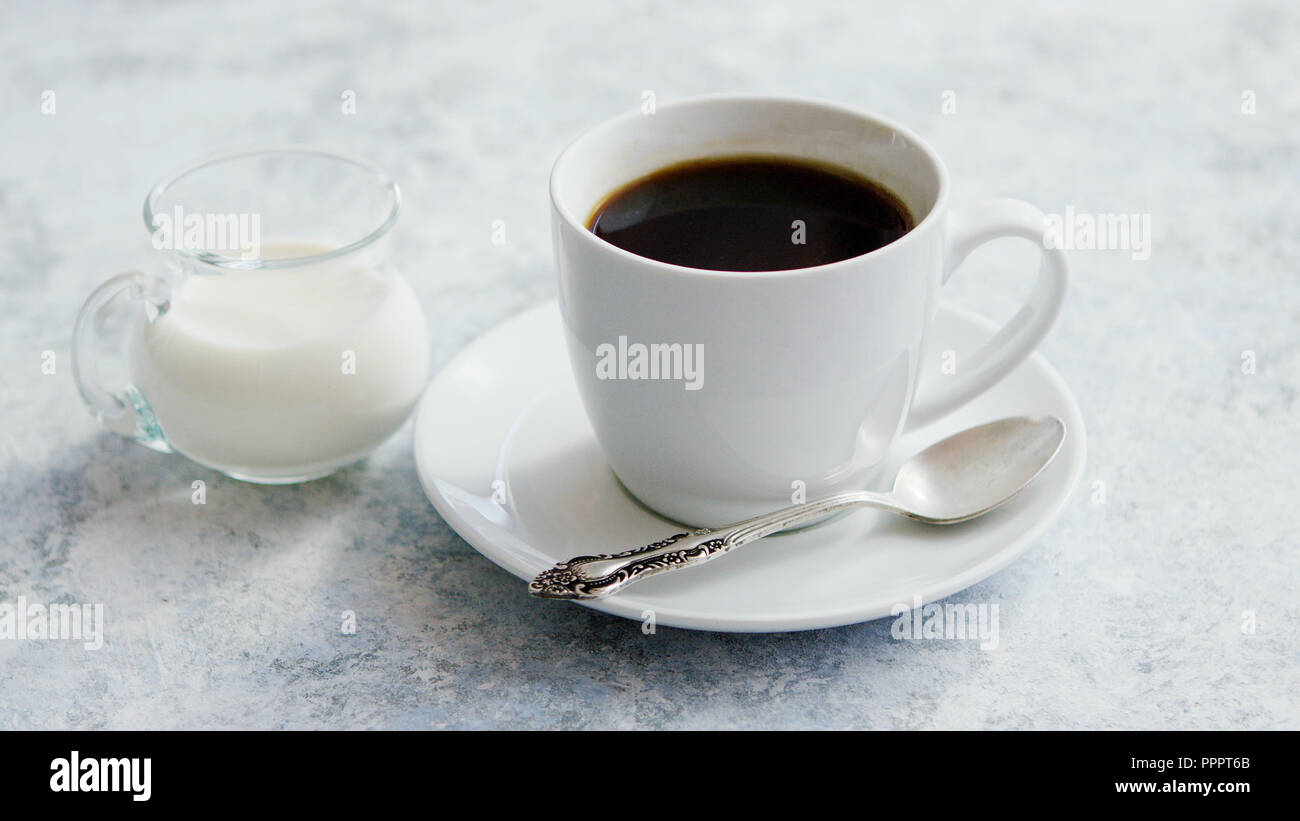 Cup of coffee and pitcher of milk - Stock Image