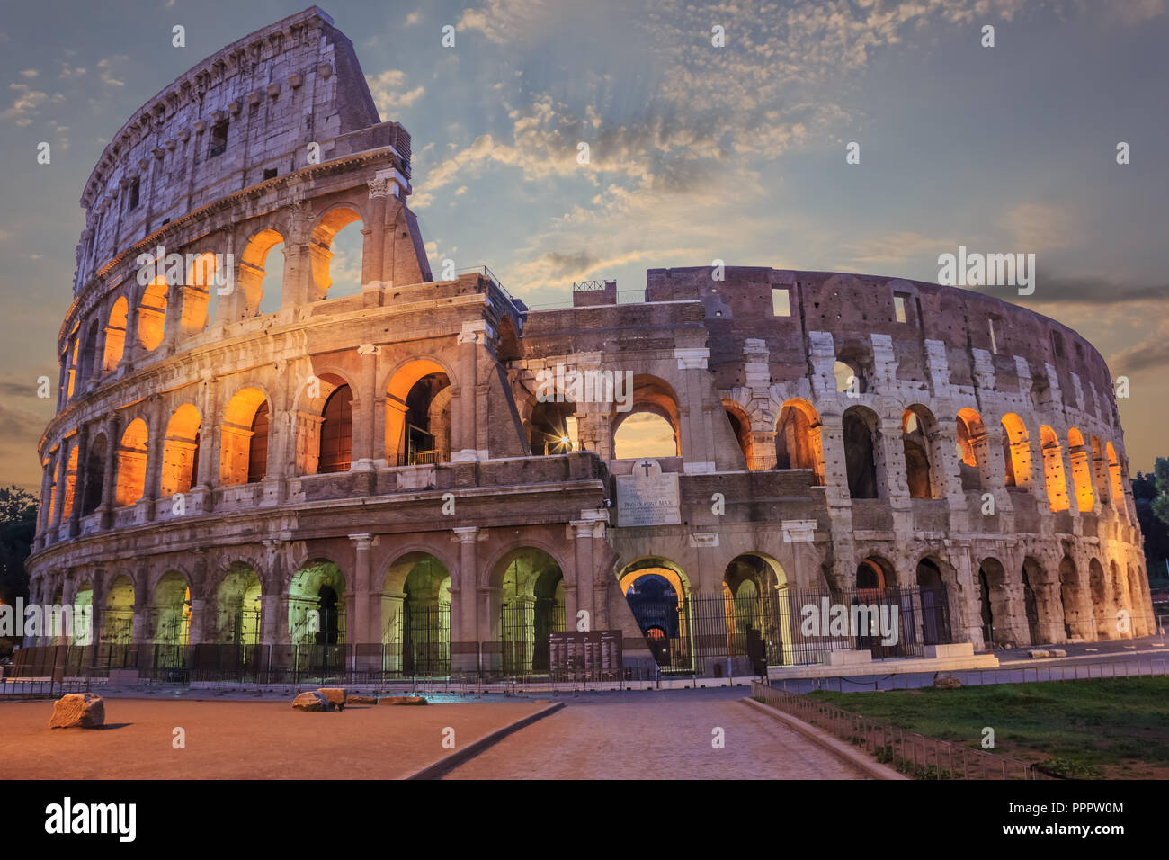 Roman Coliseum enlighted in the evening under the clouds - Stock Image