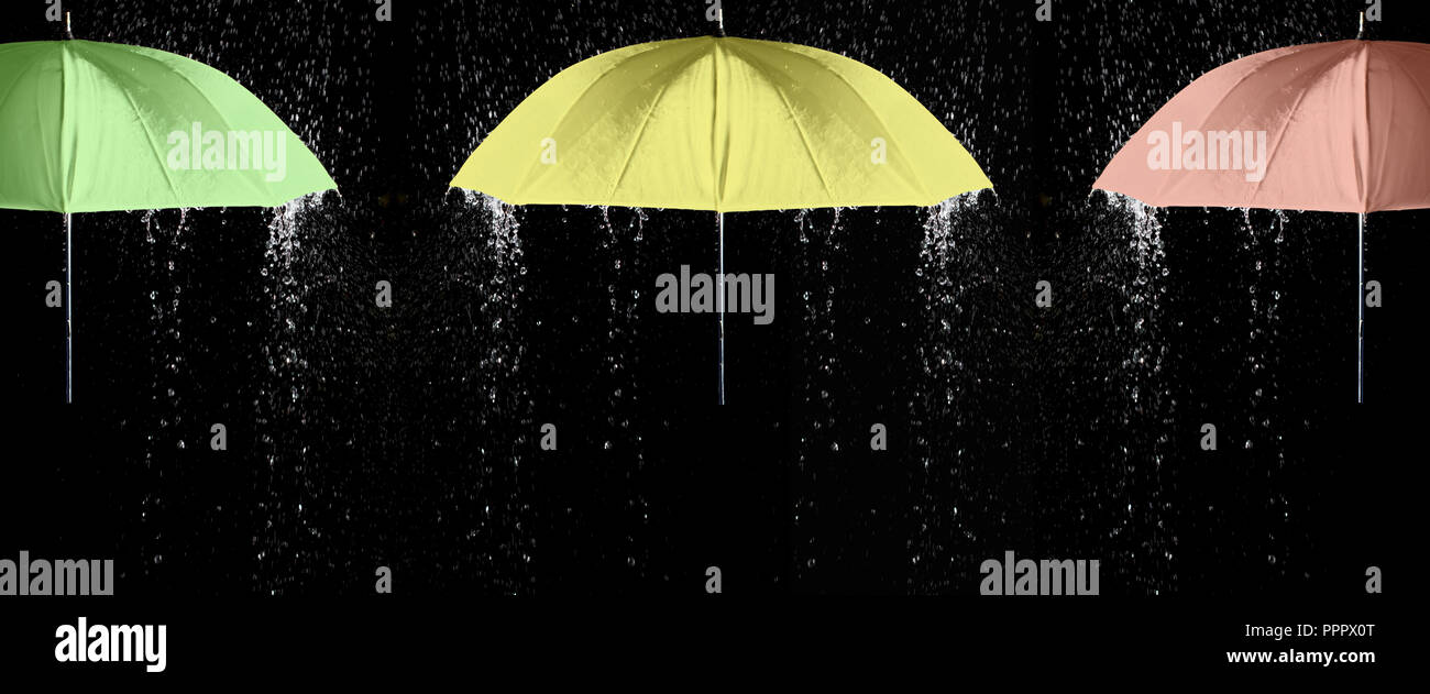 3a4d2fe33c725 Green, yellow and red umbrellas under raindrops with black background.  Business and fashion concept