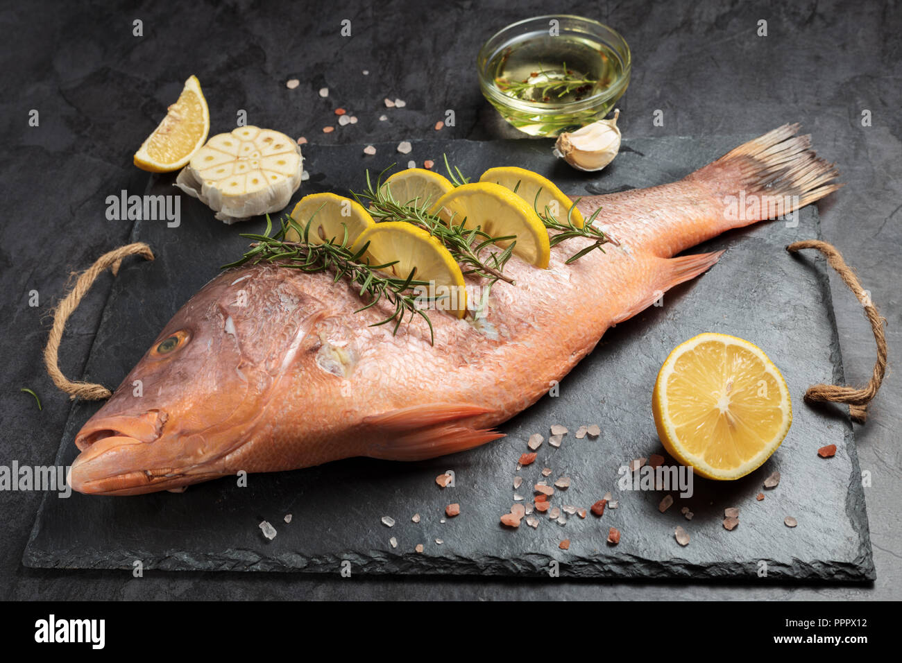 Freshly marinated raw Red snapper fish with lemon slices, garlic and rosemary herbs, on dark background Stock Photo