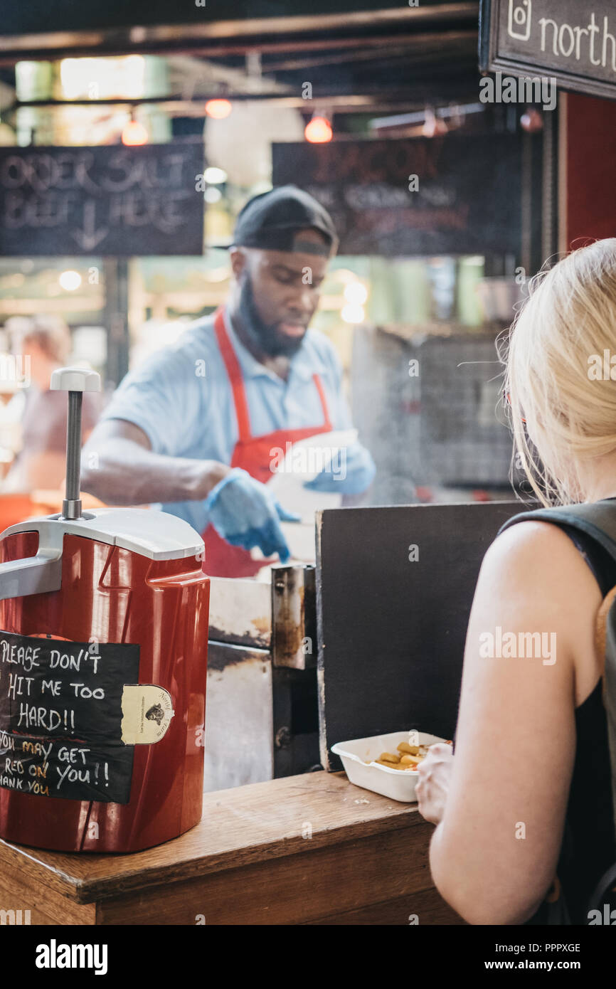 London, UK - September 17, 2018: Woman waiting for her food at Northfield Butchery stand in Borough Market, staff cooking on the background. Borough M - Stock Image