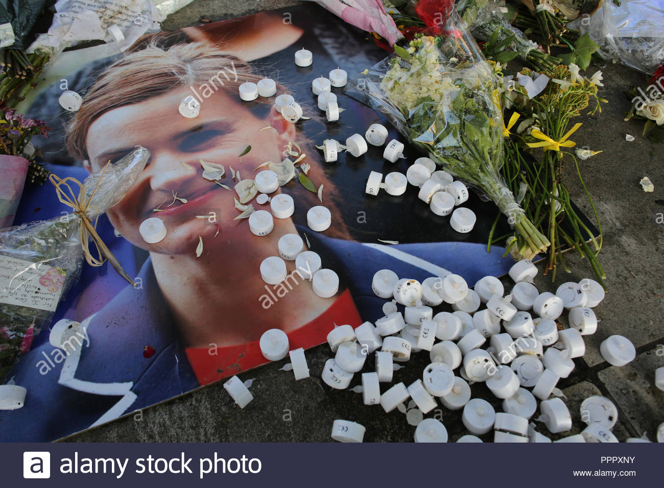 Flowers and candle holders strew across a photograph of Jo Cox in London. - Stock Image