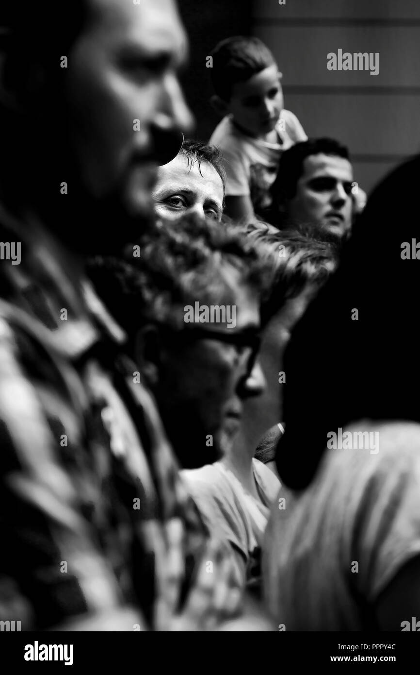 Man in crowd looking suspiciously ( at the camera) - Stock Image