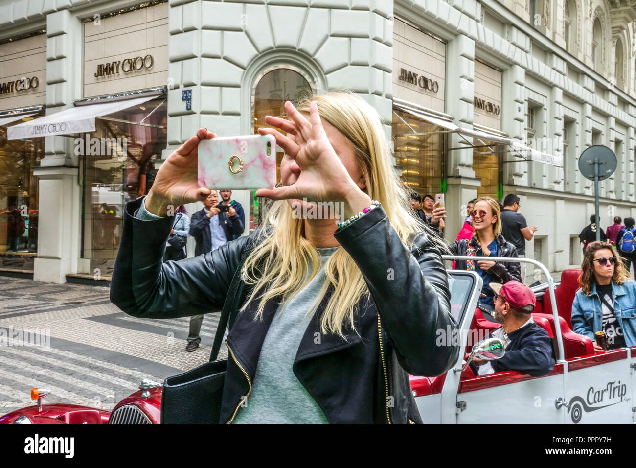Young woman taking photos in front of Jimmy Choo luxury store, Parizska street, Prague, Czech Republic - Stock Image